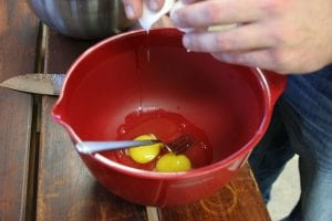 meat loaf addign eggs into the mixing bowl
